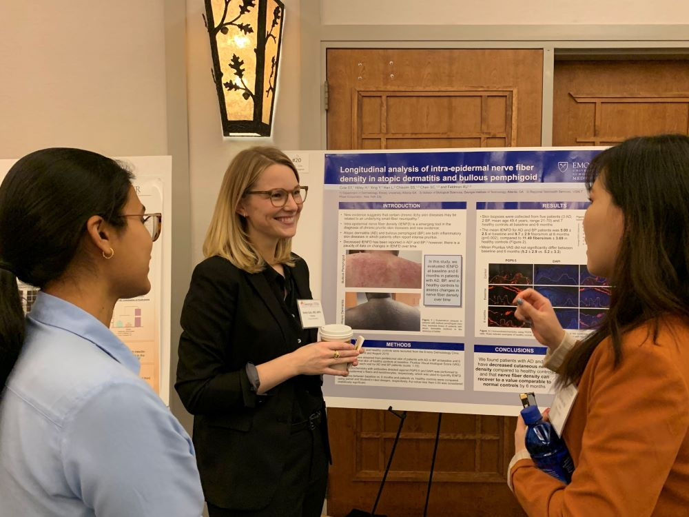 researchers presenting poster to two fellow researchers