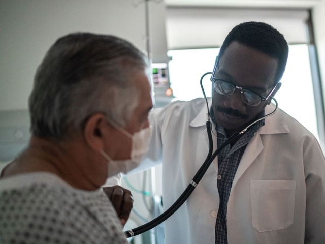 doctor listening to man's heart